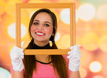 Closeup portrait of cute young girl clown mime holding wooden frame in front of her face Royalty Free Stock Photos