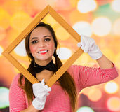 Closeup portrait of cute young girl clown mime holding wooden frame in front of her face Royalty Free Stock Photo