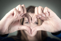 Closeup portrait of cute young teen girl making a. Heart with her fingers selective focus Stock Photos
