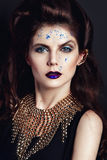 Closeup portrait with deep blue eye, creative makeup and golden accessories Royalty Free Stock Photography