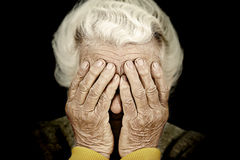 Closeup portrait depressed old woman covering her face with hand Royalty Free Stock Photography