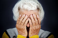Closeup portrait depressed old woman covering her face with hand Stock Photo