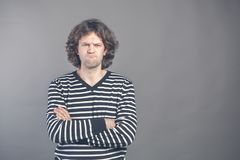 Closeup portrait displeased, angry grumpy man in striped sweater bad attitude, arms crossed, folded, looking at you, isolated gray royalty free stock photo