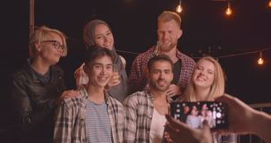 Closeup portrait of diverse multiracial group of friends being photographed on phone at fun party in cozy evening with. Fairy lights stock video footage