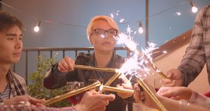 Closeup portrait of diverse multiracial group of friends celebrating lighting firework sticks at party in cozy evening.  stock video