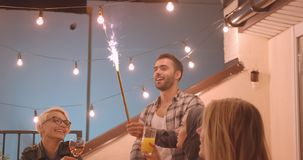 Closeup portrait of diverse multiracial group of friends eating pizza and drinking wine with firework stick at party in. Cozy evening stock video