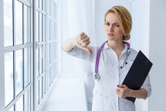 Closeup portrait, doctor woman, giving thumbs down gesture Royalty Free Stock Image