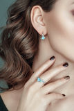 Closeup portrait of ear and hand and beautiful jewelry on it. Jewelry set of earrings and ring with gemstone. stock photo