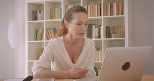 Closeup portrait of elderly caucasian brunette businesswoman having a video call on the laptop in the office indoors.  stock video