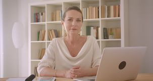 Closeup portrait of elderly caucasian brunette businesswoman looking at camera smiling happily sitting in front of the. Camera in the office indoors stock video footage