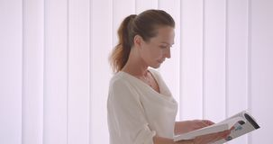 Closeup portrait of elderly caucasian brunette businesswoman reading a book standing in a white office indoors stock footage