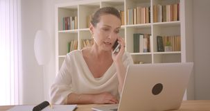 Closeup portrait of elderly caucasian brunette businesswoman using the laptop and having a conversation on the phone in. The office indoors stock video footage