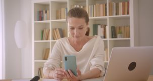 Closeup portrait of elderly caucasian brunette businesswoman using the laptop and having a video call on the phone in. The office indoors stock footage
