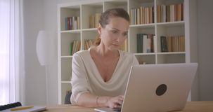 Closeup portrait of elderly caucasian brunette businesswoman using the laptop looking at camera in the office indoors.  stock video footage