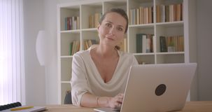 Closeup portrait of elderly caucasian brunette businesswoman using the laptop looking at camera smiling cheerfully in. The office indoors stock video footage