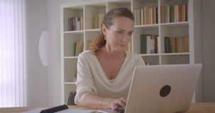 Closeup portrait of elderly caucasian brunette businesswoman using the laptop in the office indoors.  stock video footage