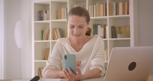 Closeup portrait of elderly caucasian brunette businesswoman using the laptop and taking selfies on the phone in the. Office indoors stock video