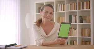 Closeup portrait of elderly caucasian brunette businesswoman using the tablet and showing green chroma screen to camera. In the office indoors stock video footage