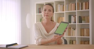 Closeup portrait of elderly caucasian brunette businesswoman using the tablet and showing green screen to camera in the. Office indoors stock video footage