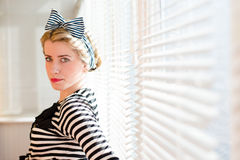Closeup portrait of elegant pinup girl having fun posing & looking at camera on sun lighting blinds windows. Beautiful blond young woman having fun posing & Stock Images
