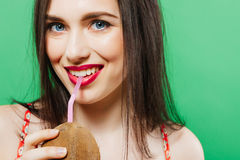 Closeup Portrait of Emotional Coquette Drinking Tropical Cocktail on Green Background in Studio. Sensual Girl is Looking at the Camera. Summer Holiday Concept Stock Photography