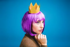 Closeup portrait fashionable young serious woman in golden crown on blue background. Cut purple hair, true emotions royalty free stock photo