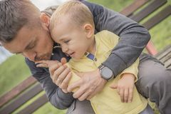 Closeup portrait of father and crying child in park. Closeup portrait of a young father and crying kid on playground. Young father hugs crying child. Dad and son stock photography