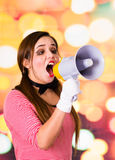 Closeup portrait of female clown mime screaming with a megaphone. Over a colorful background Royalty Free Stock Photo