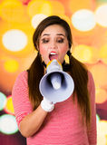 Closeup portrait of female clown mime screaming with a megaphone. Over a colorful background Stock Image