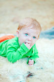 Closeup portrait with fingers in the mouth. Closeup portrait of a cute blond baby biting his fingers while staring in curiousity Royalty Free Stock Images