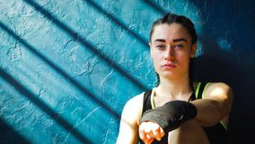 Closeup portrait fit white female boxer sitting on floor near wall resting after training at gym. royalty free stock images