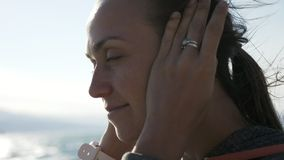 Closeup portrait of fitness woman putting on sport in-ear wireless headphones. stock video
