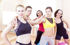 Closeup Portrait of Five Happy Caucasian Female Athletes Posing Together Embraced Against Fitballs in Gym. Royalty Free Stock Photo