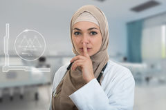 Closeup portrait of friendly, confident muslim with hijab doctor showing shh sigh, silence. Royalty Free Stock Photography