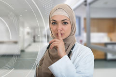 Closeup portrait of friendly, confident muslim with hijab doctor showing shh sigh, silence. Stock Photo