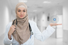 Closeup portrait of friendly, smiling confident Muslim female doctor holding medical symbols