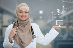 Closeup portrait of friendly, smiling confident Muslim female doctor pointing arm.