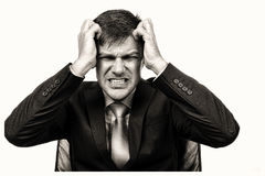Closeup portrait of a frustrated businessman pulling his hair Stock Photo