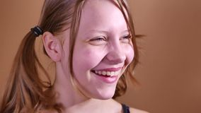 Closeup portrait of a funny attractive laughing teen girl. 4K UHD stock video footage