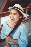 Closeup portrait of funny beautiful smiling white Caucasian brunette girl winking showing tongue, in blue dress and straw hat Stock Photo