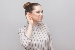 Closeup portrait of funny beautiful young woman in striped shirt and brown collected ban hairstyle, standing with hand near ear. And trying to listen. indoor stock photo