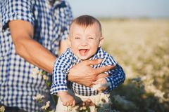 Funny happy laughing toothless caucasian baby. Closeup portrait of funny happy laughing toothless caucasian baby in hands of strong daddy. Father throwing cute Royalty Free Stock Photography