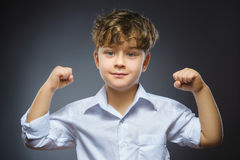Closeup Portrait of Funny Little child. Sport Handsome Boy. Strong serious kid showing his hand biceps muscles royalty free stock images