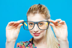 Closeup Portrait of Funny Smiling Blonde Woman with Ponytail Wearing Colorful Shirt and Fashionable Eyeglasses on Blue. Closeup Portrait of Smiling Blonde Woman Royalty Free Stock Photography