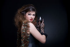 Closeup portrait of girl. Closeup portrait of beautiful girl in black gloves with red lips, tinsel and wineglass on black Royalty Free Stock Photography