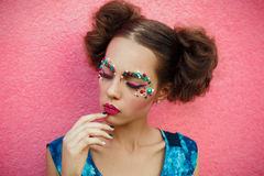 Closeup portrait of girl closed eyes and creative professional unusual fashionable makeup.Picture of pretty girl with hair in two Stock Photography