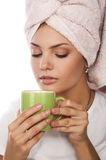 Closeup portrait of girl with cup. A beautiful young sexy nice woman with towel on head drinking coffee, isolated over white Stock Photo