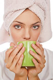 Closeup portrait of girl with cup. A beautiful young sexy nice woman with towel on head drinking coffee, isolated over white,look in to camera Royalty Free Stock Images