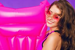 Closeup portrait of girl with long curly hair in pink sunglasses on purple background with pink mattress near in studio royalty free stock images