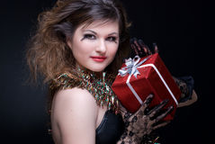 Closeup portrait of girl with present. Closeup portrait of beautiful girl with red lips, tinsel and present on black Royalty Free Stock Photography